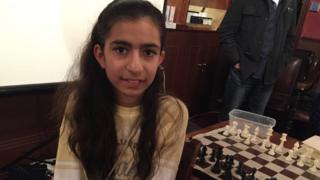 Jiya next to chessboard