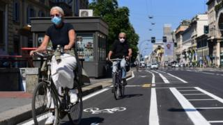 in_pictures People ride their bicycle through a bike lane in central Milan on 4 May