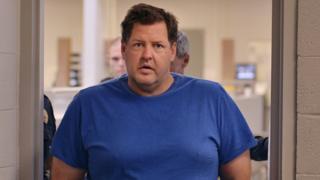 Hombre vestido con una camiseta azul camina a través de una ventana.