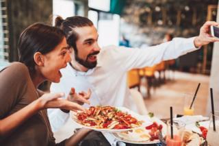 Пар у ресторану прави селфи