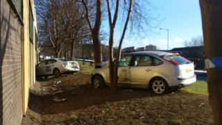 Car in wall and car against tree