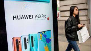 A woman walks past a bus stop ad for a Huawei smartphone in London
