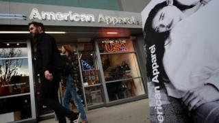 A man walks by an American Apparel store