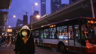 A Chinese office worker wears a protective mask as she waits to take a public bus after leaving work on 2 March 2020 in Beijing, China