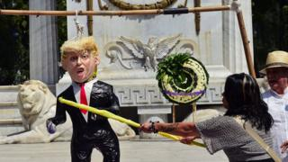 A woman hits a pinata of Donald Trump during a protest in Mexico City, on October 12, 2016