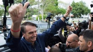 Jair Bolsonaro gives his thumbs up after casting his vote at Villa Militar,