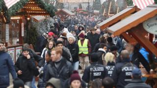 Visiteurs et policiers en marche à la réouverture du marché Breitscheidplatz non loin du lieu de l'attentat au camion