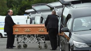 Coffins are taken to hearses in, Barconey, Ballyjamesduff in Cavan, 29 August 2016