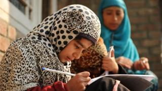 Kashmiri students study outside a house on the outskirts of Srinagar on November 2, 2016.