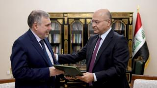 President Barham Salih (R) instructs new Prime Minister Mohammed Tawfiq Allawi
