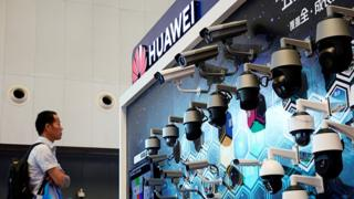 A man stands in front of a Huawei display of security cameras