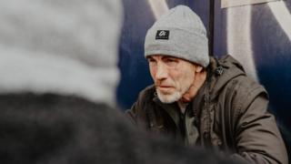 Homeless man wearing Outside In hat