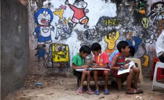 In this picture taken on September 2, 2015, Indian students sit alongside a wall covered with paintings at an art school in Nangloi, a colony in west New Delhi.