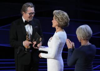 Gary Oldman onstage accepting his Oscar from Jane Fonda