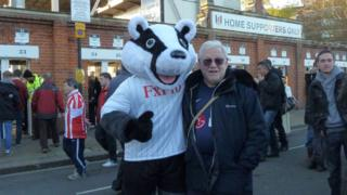 Jonathan Kotler with Billy the Badger, Fulham FC's mascot, outside Craven Cottage in west London