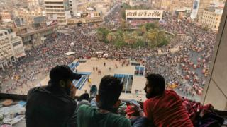 Protesters sit on top of a building near Tahrir Square in central Baghdad (28 October 2019)