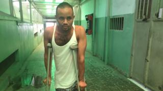 Leonel Windi on crutches in a corridor of the general hospital in Port-au-Prince