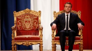Emmanuel Macron sandalyede oturuyor