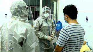 Nhân viên y tế trong trang phục bảo vệ trao đổi với bệnh nhân đã cho kết quả dương tính với virus corona trong phòng cách ly tại Bệnh viện Chợ Ray, TP HCM,hôm 23/1
