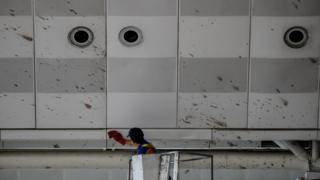 A worker cleans the blood splashed on the roof of the international departure terminal at Istanbul's Ataturk airport
