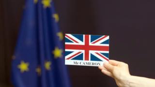 Una tarjeta con la bandera británica y el nombre de David Cameron frente a una bandera de la Unión Europea.