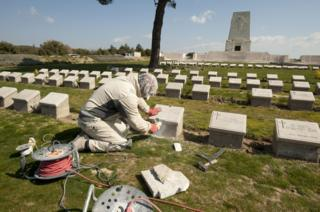 A person in a headscarf uses electric tools to repair a plinth at Lone Pine Cemetery in Gallipoli, Turkey
