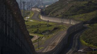 The existing barricade - made of steel wall, fences, and razor wire - is seen winding along the US-Mexico border in San Ysidro, California.