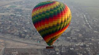 A hot-air balloon flies over the city of Luxor, south of Cairo, Egypt December 13, 2016.
