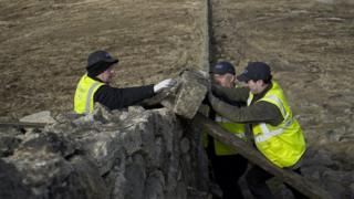 Stonemasons lifting a stone on to the Mourne Wall