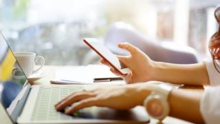 Young woman looking at smartphone while using laptop