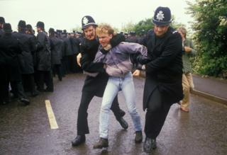 Two policemen restrain a miner, Orgreave 1984
