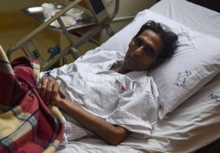 Mansoor Ahmed lying on his hospital bed in Karachi.