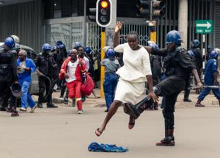 in_pictures A riot police officer attacks a woman in Harare, Zimbabwe - Wednesday 20 November 2019