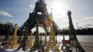 Miniatures of the Eiffel Tower are sold as souvenirs on a street of Paris at the foot of the monument