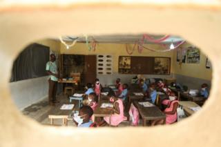 Pupils, wearing protective masks, are photographed through the window during a lesson.