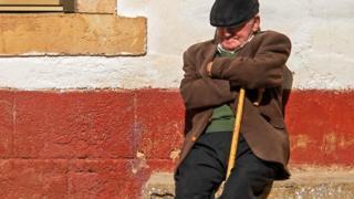 Un hombre tomando la siesta recostado de una pared