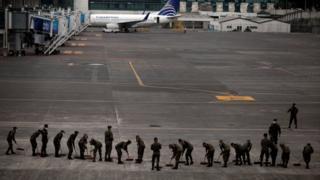 """Головний аеропорт """"Ла Аурора"""" закрили. На цьому фото солдати згрібають попіл, яким засипало летовище"""