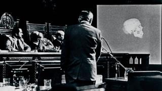 Hombre habla durante un juicio. En una pantalla se exhibe un cráneo.