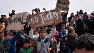 ギリシャ・ヒオス島で「トルコはいやだ」とメッセージを掲げる移民の少年