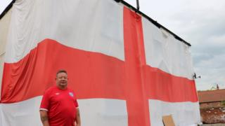 John Jupp standing in front of his huge England flag