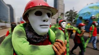 Endonezyalı işçiler, protestolarda maskelerle yürüdü.