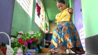 بانو أكتار من بنغلاديش، ولدت من دون ذراعين وأهملتها عائلتها. لكن ذلك لم يمنعها من الالتحاق بالمدرسة وتعلم حرفة تدر عليها مالا مستخدمة أصابع قدميها فقط.
