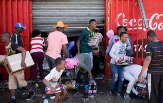 Looters take goods out of a store
