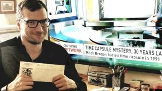 Technology Mitch Brogan holding up the time capsule envelope
