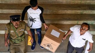 Police and electoral officials look on as they collect ballot papers and boxes from a distribution centre for their respective polling stations on the eve of the presidential election, in the southern town of Hambantota some 256 kms from Colombo on November 15, 2019