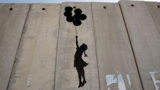 Trabalho de Banksy na parede que separa Israel mostra a silhueta de uma garota suspensa por com balões