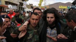 A Lebanese soldier helps a fellow member of the security forces held captive by al-Nusra Front moments after his release on 1 December 2015, in the village of Labweh, Lebanon