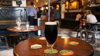 Imagem mostra cerveja e pessoas em um pub