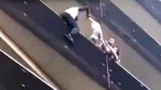 Imagen del video cuando Mamoudou Gassama llega al cuarto piso sujeta el niño