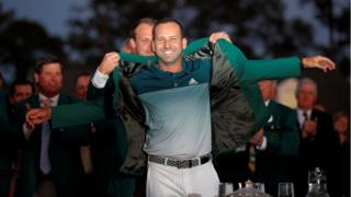 Sergio Garcia of Spain is presented the green jacket by last year's champion, Danny Willett of England